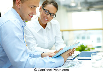 Young businessman looking at touchpad with his secretary near by