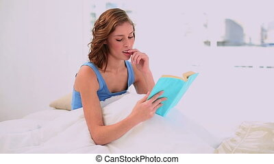 Pleased woman reading a book