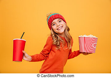 Pleased Young girl in sweater and hat holding popcorn