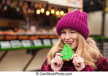 Pleased young woman eating delicious christmas gingerbread at the street in Kiev
