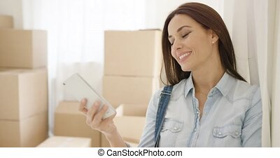 Pleased attractive happy young woman talking on a mobile phone as she leans against the wall in her new home surrounded by brown boxes