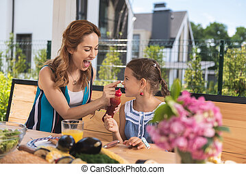 Pleasant happy woman playing with her daughter