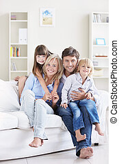 Pleasure - A happy family with children on a white sofa at...