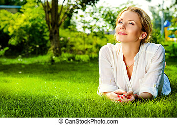 pleasure - Beautiful smiling woman lying on a grass outdoor....