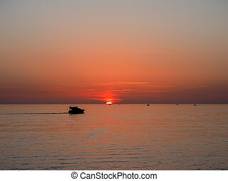 Pleasure boat against the backdrop of a beautiful sea sunset