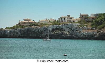 Pleasure boat swims into the bay in a provincial town Porto Cristo. Mallorca
