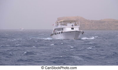 Pleasure Boat with Tourists Sails in the Stormy Sea on the...