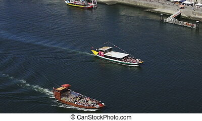 Pleasure boats with tourists sailing on the Douro River in Porto.