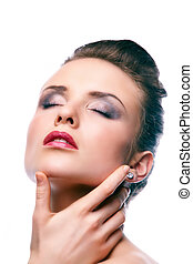 Gorgeous young woman with closed eyes touching her face