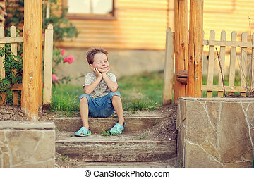 the happy boy sits on a porch of the wooden house
