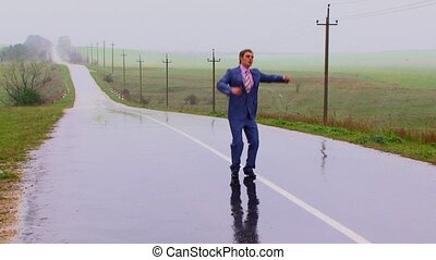 There is a strong rain. The guy jumps up for pleasure. Shows a pleasure sign. The joyful young man jumps through a dividing strip in a road distance. Comes nearer to the camera. Its reflexion on wet asphalt.