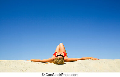 Pleasure - View of beautiful woman lying on the sand getting...