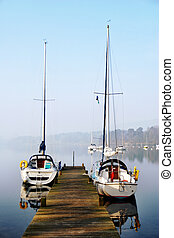 Pleasure yachts moored on rustic jetty - Two small pleasure...
