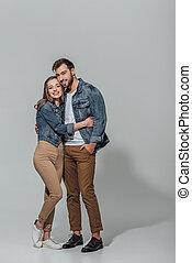 plena vista comprimento, de, alegre, par jovem, abraçando, e, sorrindo, câmera, isolado, ligado, cinzento