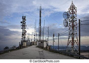 Plenty of radio masts located on the hilltop with antennas. ...