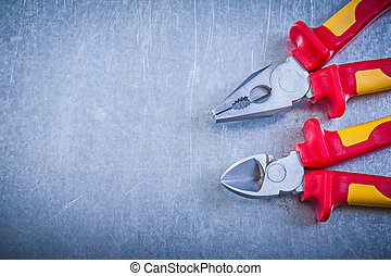 Pliers nippers on metallic background copyspace electricity conc