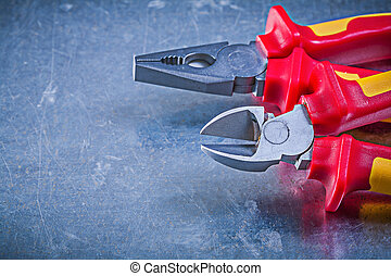 Pliers nippers on metallic background electricity concept
