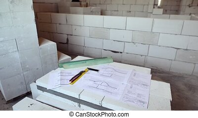 Pliers, square ruler and blueprints on construction site. -...
