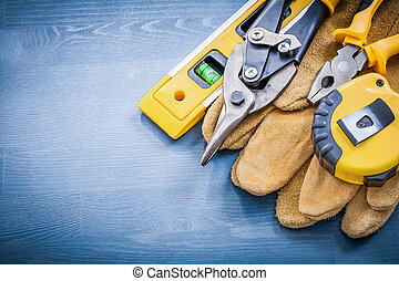 Pliers tin snips tape-measure construction level safety gloves.