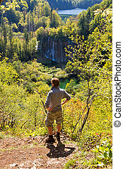 Plitvice lookout - Active young man looking at a waterfall...