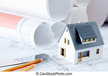 Close-up of toy house model on blueprints with ruler and two pencils near by