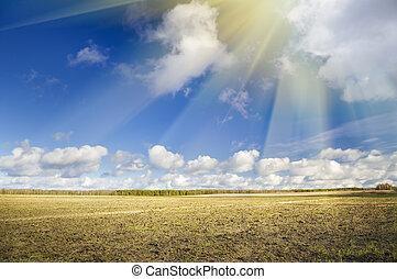 plough plowed brown clay soil field blue sky horizon