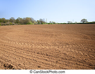 Ploughed cultivated farmland waiting for sowing of crop -...