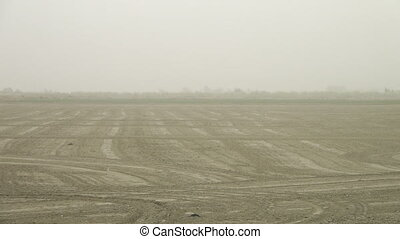 Ploughed Farmland With Low Visibility - Steady, wide shot of...