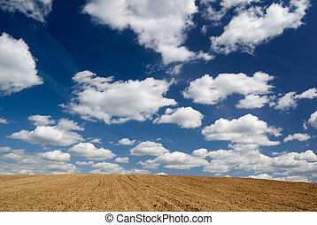 Blue sky with clouds over ploughed field.