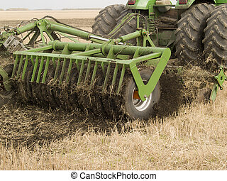 Plow - tractor pulls a plow on a green field