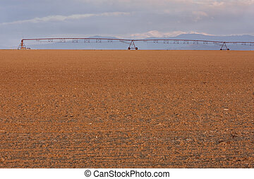 plowed field and irrigation equipment