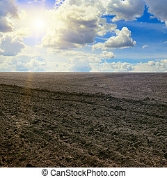 plowed field and sun on cloudy sky