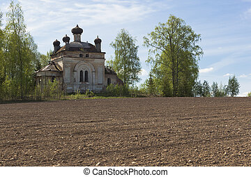 Plowed field on a background of crumbling church. Concept of rebirth of life