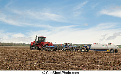 Plowing a Farm Field - Red tractor pulling plow and...