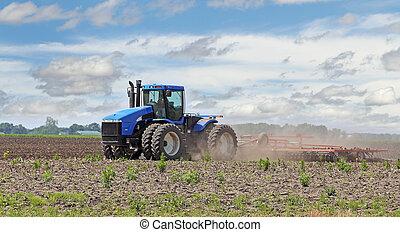 Plowing a Field - Blue tractor pulling a plow in a farm...