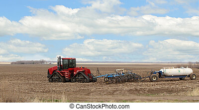 Plowing and Fertilizing - Farm tractor pulling plow and...