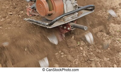 Plowing the soil with a motoblock in slow motion