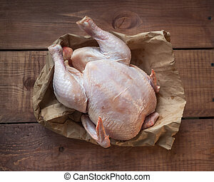 Plucked chicken carcass lies on a paper bag on a wooden table, closeup