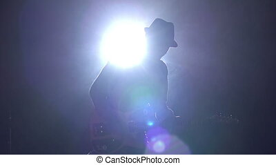 Plucking Strings of Guitar - Silhouette of guy in hat...