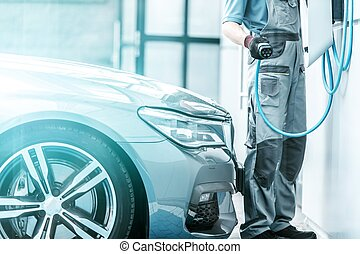 Plug In Hybrid Vehicle and the Charging Station. Worker...