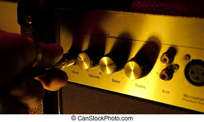 Plugging in cable into the headphone jack of amplifier. Male hand connecting and disconnecting guitar cord to amp.