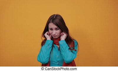 Plugging ears with fingers doesn't want to hear, covered auricle hands, displeased, block the sound, something is loud. Young attractive woman with brown hair and eyes, decoration on blue shirt
