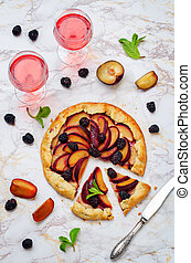 Plum blackberry galette on a white background. toning. ...