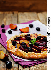 Plum blackberry galette on a wood background. toning. ...