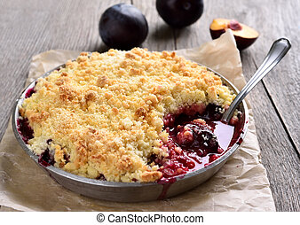 Plum crumb baking in pan on wooden background