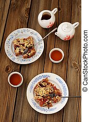 Plum crumble and black tea on wooden background