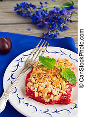 Plum crumble on the wooden background with blue flowers