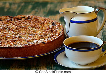 Plum crumble tart with cup of coffee and creamer on green ...
