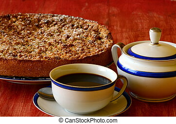 Plum crumble tart with cup of coffee and sugar bowl on red ...