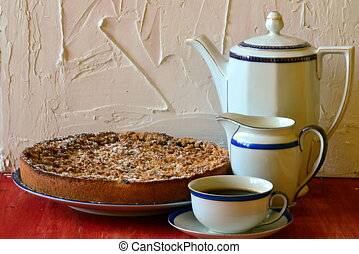 Plum crumble tart with cup of coffee, creamer and coffee pot...